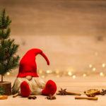 red christmas wretch next to fir tree and cinnamon sticks